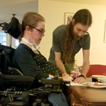 Woman in a wheelchair and a man at a table.