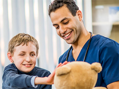 A Doctor and young boy playing with a teddy bear