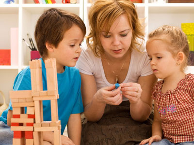 Mother working with two young children on a puzzle